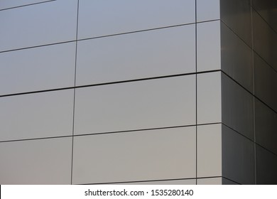 Aluminium composite cladding. The grey panel wall cladding is on the corner of a modern new building