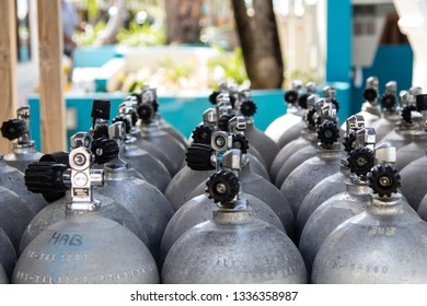 Aluminium diving tanks filled with compressed air lined up and waiting for their deployment on the beautiful reef of the caribbean island Bonaire