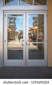 Aluminium door and chrome door handle with glass in the store