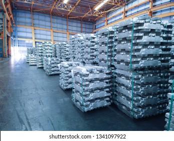 Aluminium ingot bundles stored inside industrial warehouse. Industry raw material logistics operation.