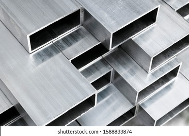 Aluminium profile for windows and doors manufacturing. Structural metal aluminium shapes. Aluminium profiles texture for constructions. Aluminium constructions factory background.