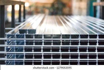 Aluminium profiles placed in a row inside an aluminium profile factory.