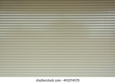 Aluminium steel metal roller shutter door in warehouse building, industrial background