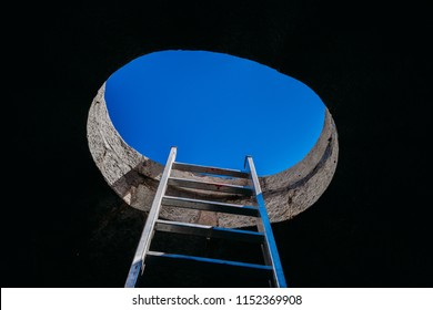 Aluminium vertical step ladder from darkness towards a window opening on ceiling with blue sky. Conceptual themes of hope, freedom, escape, peace and spirituality