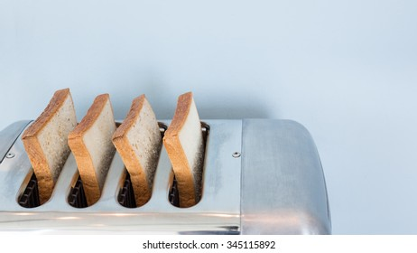Aluminum big toster with four slice of breads on light blue wall.