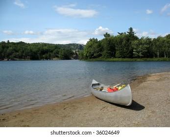 Aluminum canoe on a blue lake in the summer