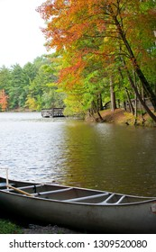 An aluminum canoe sits on a serene lake surrounded by beautiful fall foliage. Photo taken in southern Wisconsin.