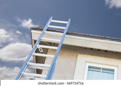 Aluminum Construction Ladder Leaning Against House.