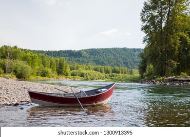 Aluminum drift boat anchored at a prime fishing spot along the McKenzie River in Oregon.