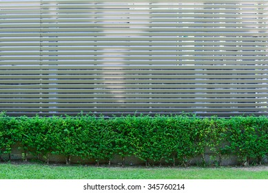 Aluminum fence with ornamental plants surrounded factory.