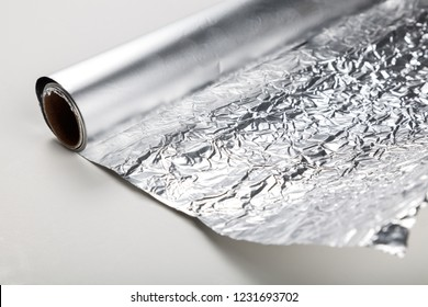 Aluminum foil roll on the white background, close up.