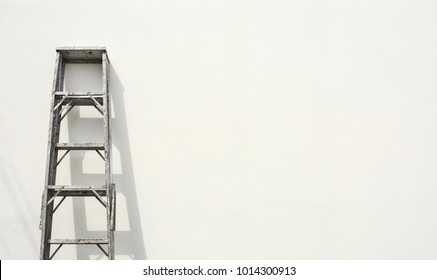 aluminum foldable ladder and the shadow at white cement wall