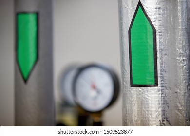 Aluminum insulated heating water pipes marked with green arrows flow directions. Measuring instruments blurred in the background. Heat distribution to households. Start of the heating season.