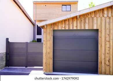 Aluminum modern home with grey gate portal and modern garage door of wooden house