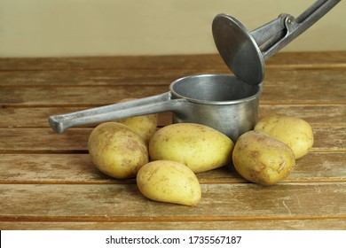 Aluminum potato masher on wooden table with potatoes.