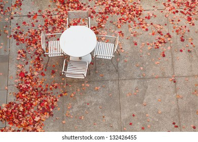 An aluminum table with four chairs surrounded by fallen red maple leaves.
