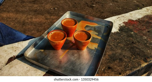 a aluminum tray carrying three pottery cups filled with Darjeeling tea