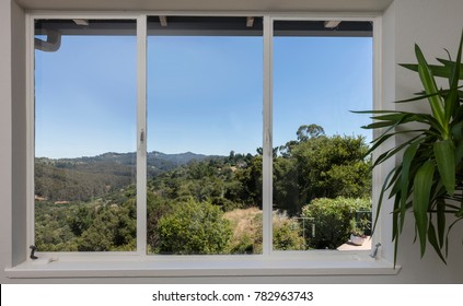 Aluminum window with cock-spur. Window handle on an aluminium window with mountain view.