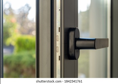 Aluminum window detail. Metal door frame open closeup view. Energy efficient, safety profile, blur green outdoor background