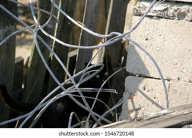 Aluminum wire lies in the village near the fence