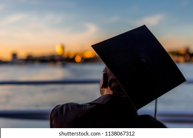 Alumni watching sunset after graduation with blurred urban background reflecting a deep orange light and railing on waterfront in the foreground with a blue sky
