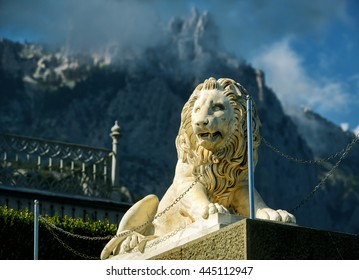 ALUPKA, CRIMEA - MAY 20, 2016: Statue of lion at Vorontsov Palace on the background of misty Mount Ai-Petri in Crimea, Russia. It is a tourist attraction of Crimea. Architecture and nature of Crimea.