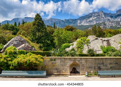 Alupka, Crimea - May 20, 2016: Garden at the Vorontsov Palace in Crimea, Russia. It is one of the main landmarks of Crimea. Mount Ai-Petri in the distance. Beautiful panoramic view of Crimea coast.