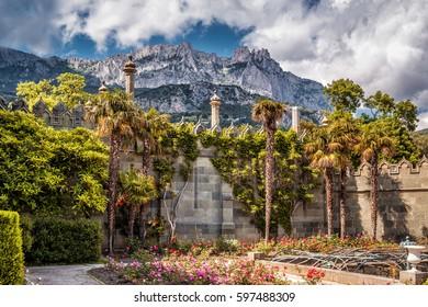 ALUPKA, CRIMEA - MAY 20, 2016: The garden in the Vorontsov Palace in Crimea, Russia. Mountain Ai-Petri in the distance. Vorontsov Palace is one of the main tourist attractions of Crimea.