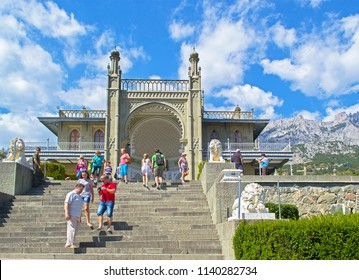 Alupka, Russia - 8 Sep 2016: Southern facade of Vorontsov Palace with 'Lions' terrace against picturesque mountains & blue sky with clouds. View of Ai-Petri peaks.