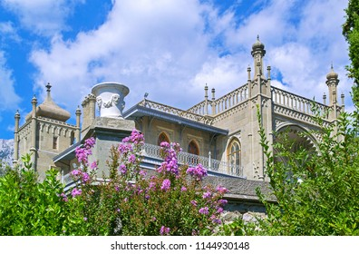 Alupka, Russia - 8 Sep 2016: Towers of Vorontsov Palace on southern facade in oriental style against blue sky. Blossoming oleander treee & old stone vase.