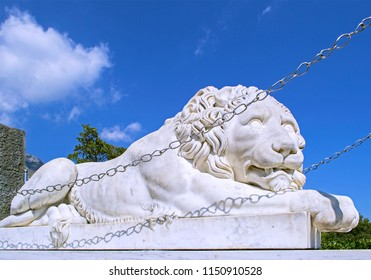 Alupka, Russia - 8 Sep 2016: Marble statue of sleepy lion at southern facade of Vorontsov Palace. Closeup