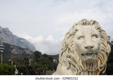 ALUPKA, RUSSIA - MAY 20, 2016: Statue of lion at the Vorontsov Palace on the background of Ai-Petri mountain. This palace is a tourist attraction of the Crimea.