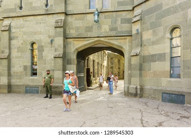 Alupka, Yalta, Crimea, Russia-September 12, 2018: Tourists under the arch of the Western entrance to the Palace of Prince Vorontsov, built in the early XIX century. Sunny summer day