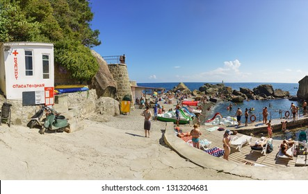 Alupka, Yalta, Crimea, Russia-September 12, 2018: popular with tourists picturesque children's beach. Large stones protect from wind and waves. The inscription on the building medical And Rescue
