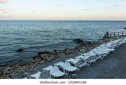 """Alupka, Yalta, Crimea, Russia-September 12, 2018: Fisherman with a fishing rod on the beach. Evening on the city deserted beach """" green Cape"""""""