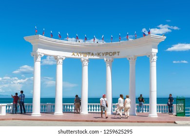 "ALUSHTA, CRIMEA - MAY 15, 2016: People visit the rotunda ""Alushta resort"" on the beach in Crimea, Russia. Scenic view of Black Sea waterfront of Crimea. White colonnade with Russian flags in Crimea."