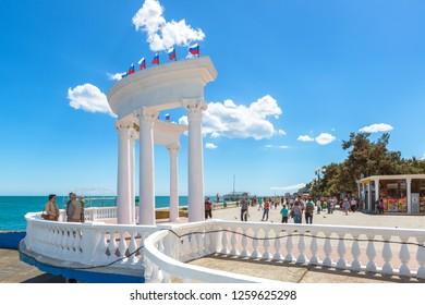 ALUSHTA, CRIMEA - MAY 15, 2016: People visit the urban beach in Crimea, Russia. Scenic view of the Black Sea waterfront in Crimea. White colonnade with Russian flags on the Southern coast of Crimea.