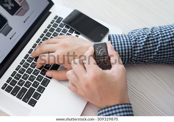 Alushta, Russia - August 14, 2015: Man hand with Apple Watch and Macbook on the desk. Apple Watch was created and developed by the Apple inc.