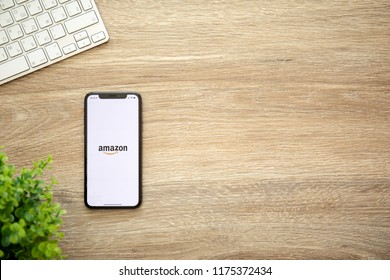 Alushta, Russia - August 22, 2018: iPhone X with Internet shopping service Amazon on the screen and background wooden desk. iPhone 10 was created and developed by the Apple inc.