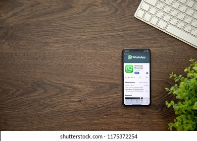Alushta, Russia - August 25, 2018: iPhone X with social networking service WhatsApp on the screen and background wooden desk. iPhone 10 was created and developed by the Apple inc.