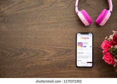 Alushta, Russia - August 25, 2018: iPhone X with social networking service Instagram on the screen and background wooden desk. iPhone 10 was created and developed by the Apple inc.