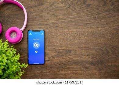 Alushta, Russia - August 25, 2018: iPhone X with music service Shazam on the screen and background wooden desk. iPhone 10 was created and developed by the Apple inc.