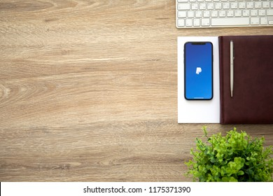 Alushta, Russia - August 26, 2018: iPhone X with service PayPal on the screen and background wooden desk. iPhone 10 was created and developed by the Apple inc.