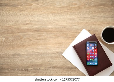 Alushta, Russia - August 26, 2018: iPhone X with social networking Messenger on the screen and background wooden desk. iPhone 10 was created and developed by the Apple inc.