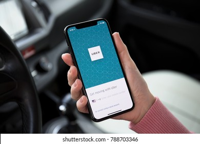 Alushta, Russia - December 16, 2017: Woman hand holding iPhone X with application Taxi Uber on the screen in the car. iPhone 10 was created and developed by the Apple inc.