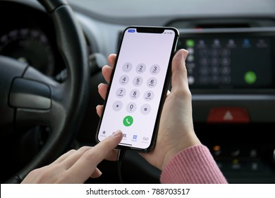 Alushta, Russia - December 16, 2017: Woman hand holding iPhone X with call number on the screen in the car. iPhone 10 was created and developed by the Apple inc.