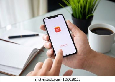 Alushta, Russia - July 27, 2018: Man holding iPhone X with Internet shopping service Aliexpress on the screen. iPhone 10 was created and developed by the Apple inc.