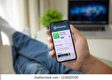 Alushta, Russia - July 29, 2018: Man holding iPhone X with social networking service WhatsApp on the screen. iPhone 10 was created and developed by the Apple inc.