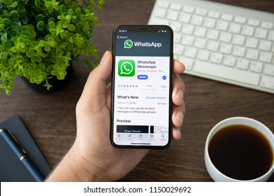 Alushta, Russia - July 30, 2018: Man holding iPhone X with social networking service WhatsApp on the screen. iPhone 10 was created and developed by the Apple inc.
