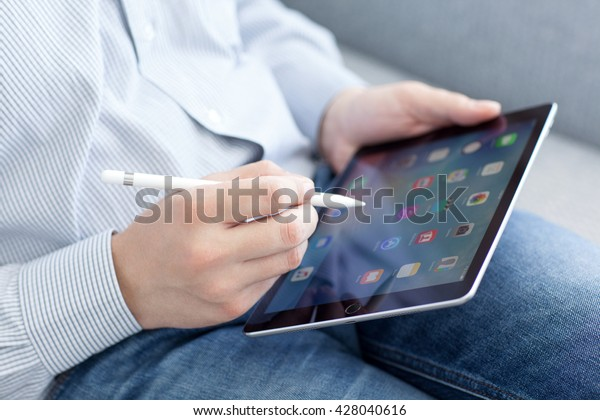 Alushta, Russia - May 14, 2016: Man with Apple Pencil holding in the hand iPad Pro. iPad Pro was created and developed by the Apple inc.